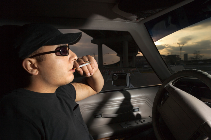 Picture of a man smoking in a car