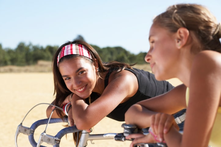 Two girls on bicycles outdoors
