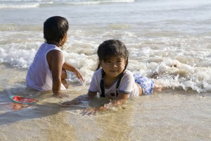 Two kids playing in shallow water at a beach.