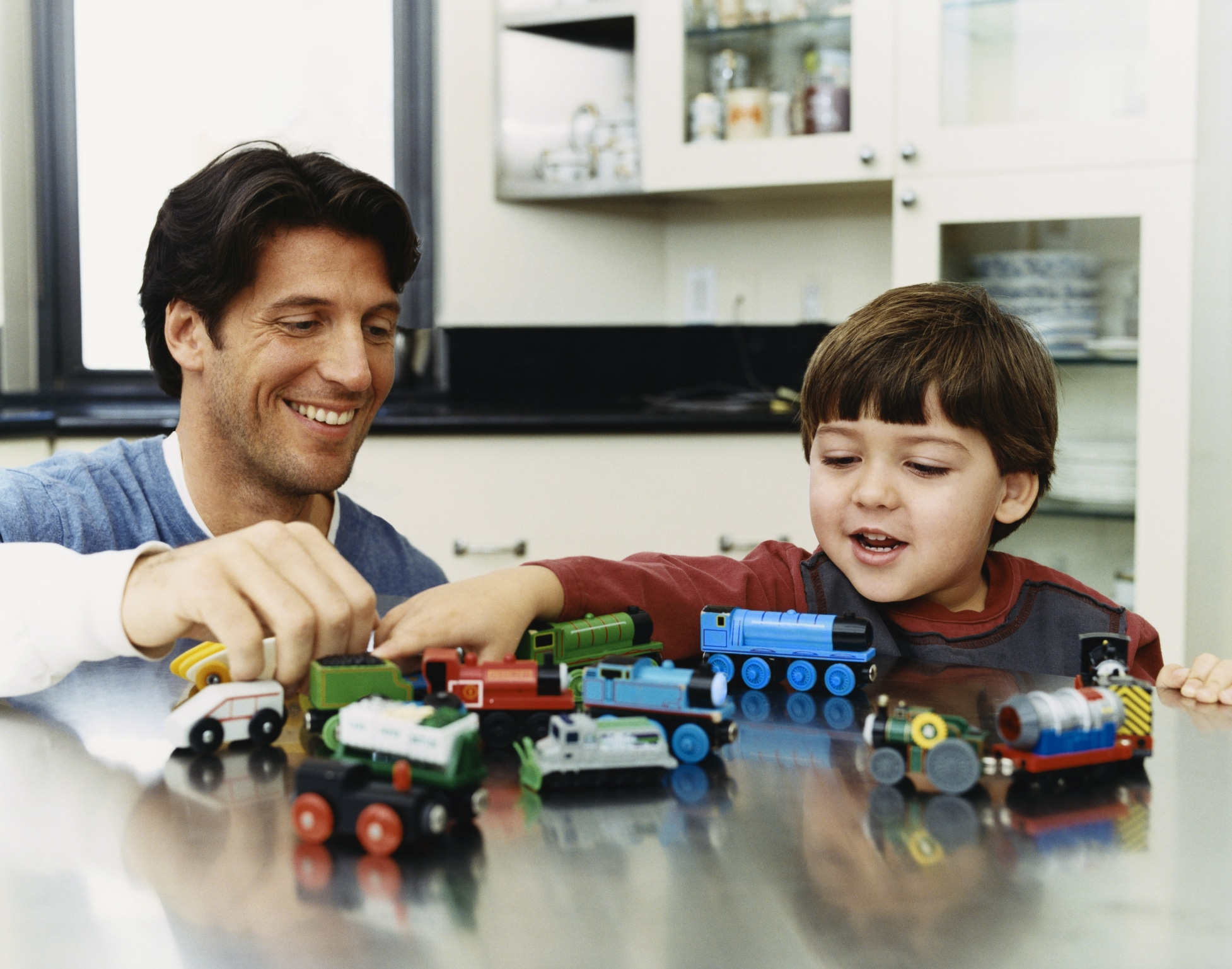 Father And Son Playing With Trains