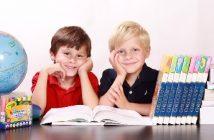 2 boys smiling at a school desk