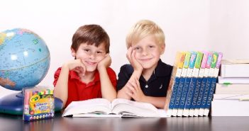 2 boys smiling at a school desk