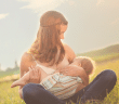 Woman sitting outside in grass breastfeeding child