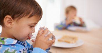 A cute little boy having a drink of water with breakfast
