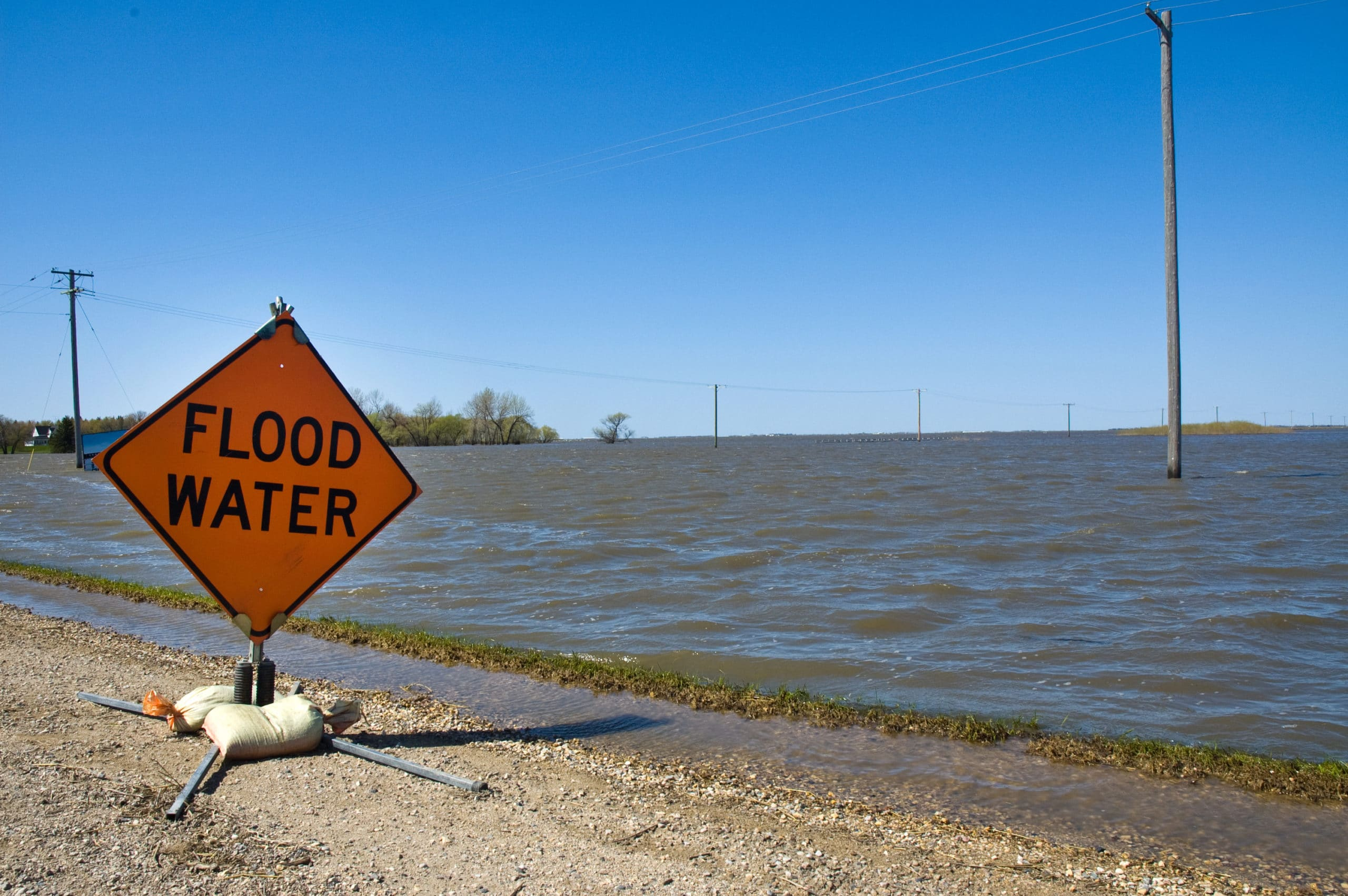 Picture of flooded field with warning sign
