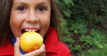 child biting an apple