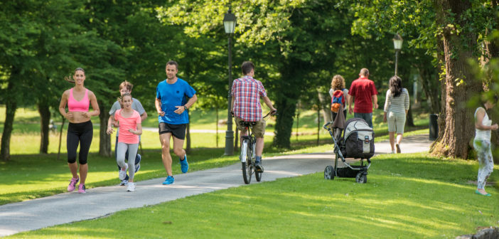 Family jogging and man cycling in park, people walking in background.