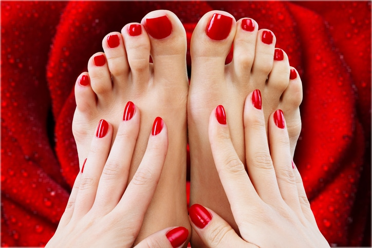 Closeup photo of a beautiful female feet with pedicure and hands with manicure