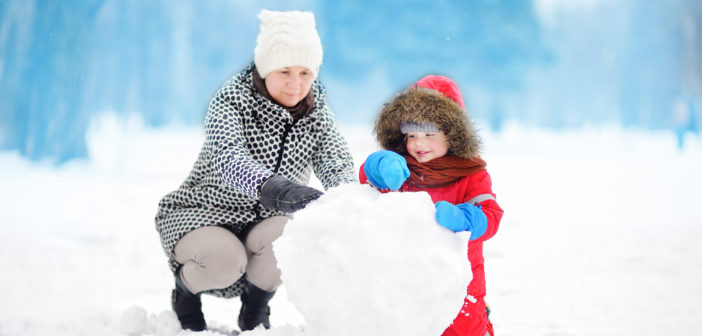 Child building a snowman with female adult