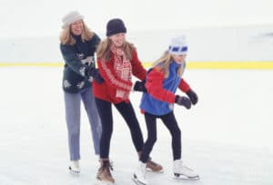 a mother and two daughters ice skating