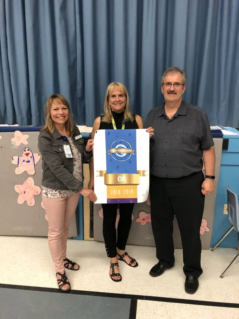 CK Public Health Nurse Lisa Tetrault stands beside Saint Francis Principal and staff, holding OPHEA Gold banner.