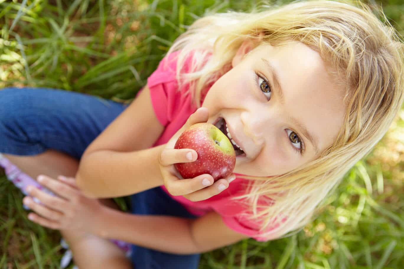 Girl eating an apple while looking up at the camera