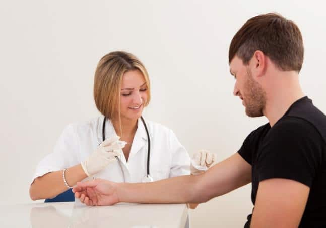 Nurse giving young male a needle