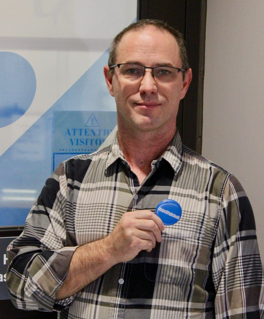 man holding a button that says CK Public Health