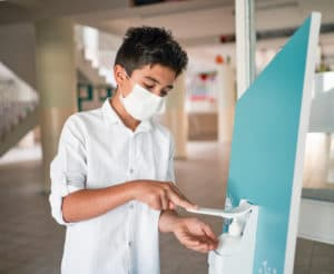 Student wearing a mask practices hand hygiene at school.