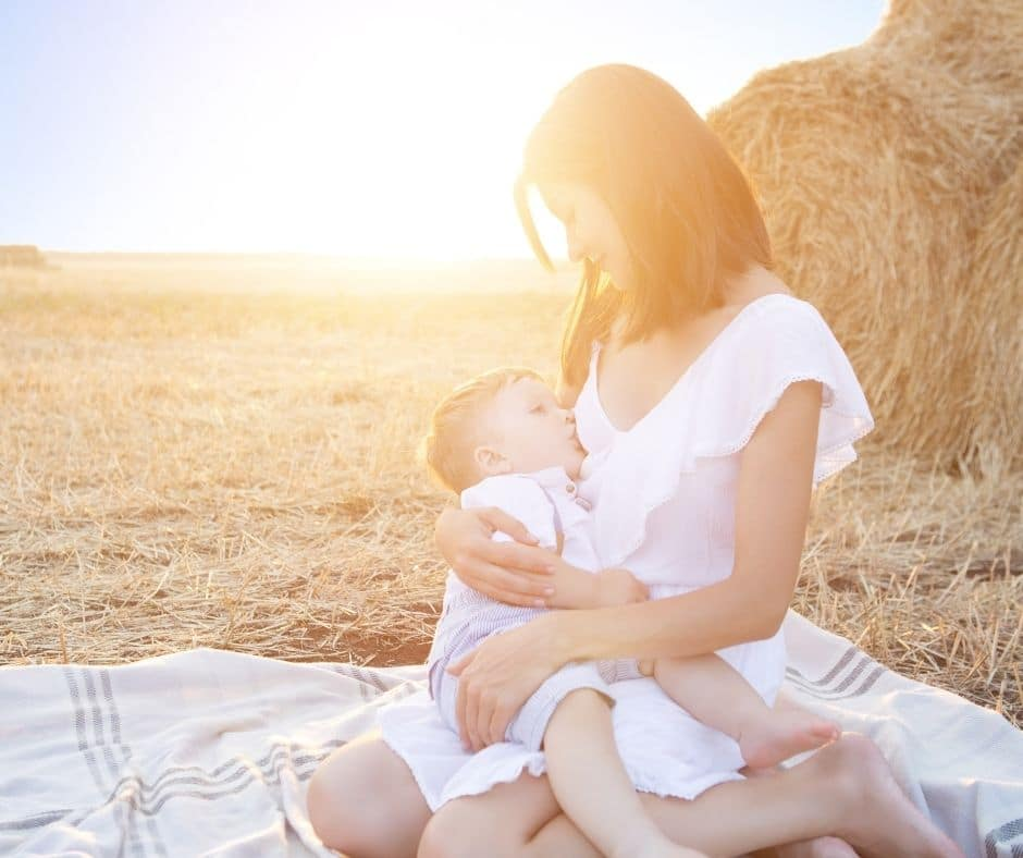 Woman breastfeeding in a wheat filed