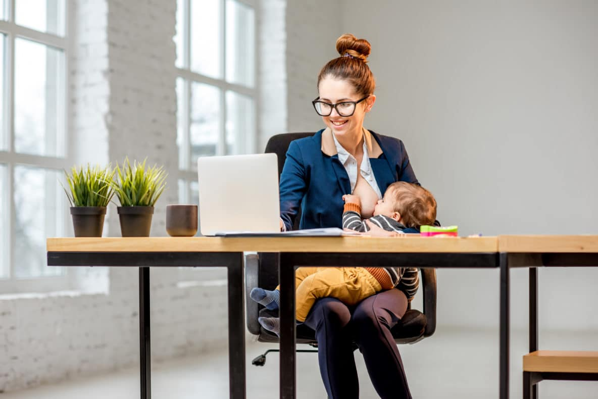 Woman breastfeeding her baby while working at the office